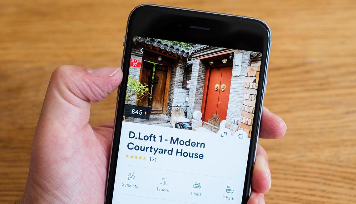 Mano sostiene un teléfono móvil con la aplicación Airbnb con una propiedad en Beijing, China