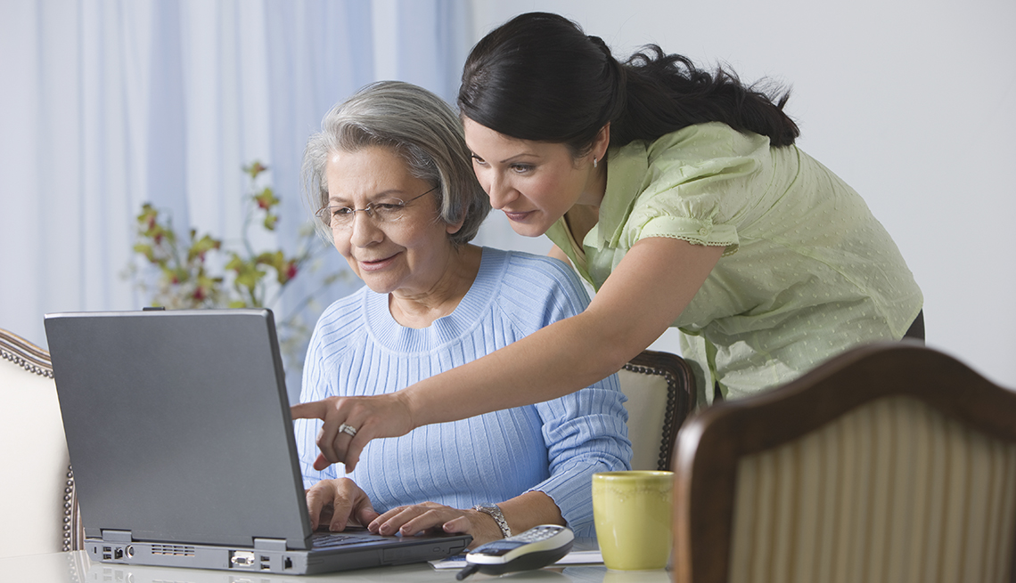 A woman showing her mother how to use a laptop