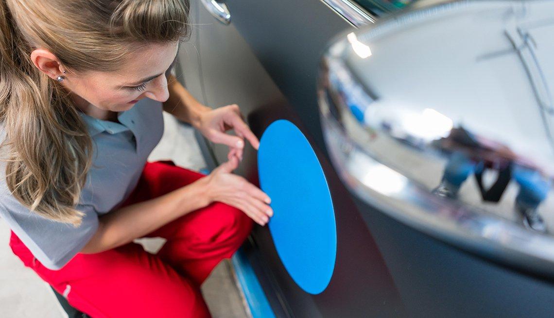 Mujer colocando una identificación con el símbolo de una companía a un carro.
