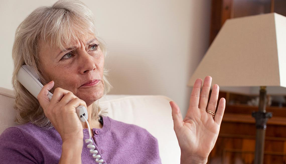 Mujer sosteniendo un auricular de teléfono desde la sala de su casa