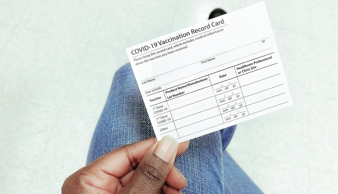Manos de una mujer mostrando la tarjeta de vacunación de la COVID-19