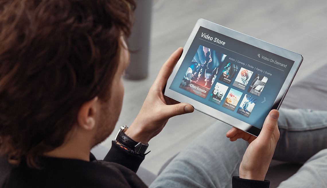Man using tablet for watching VOD service. Video On Demand television concept