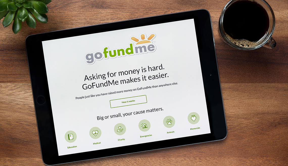 The website of GoFundMe is seen on an iPad tablet, on a wooden table along with an espresso coffee and a house plant.