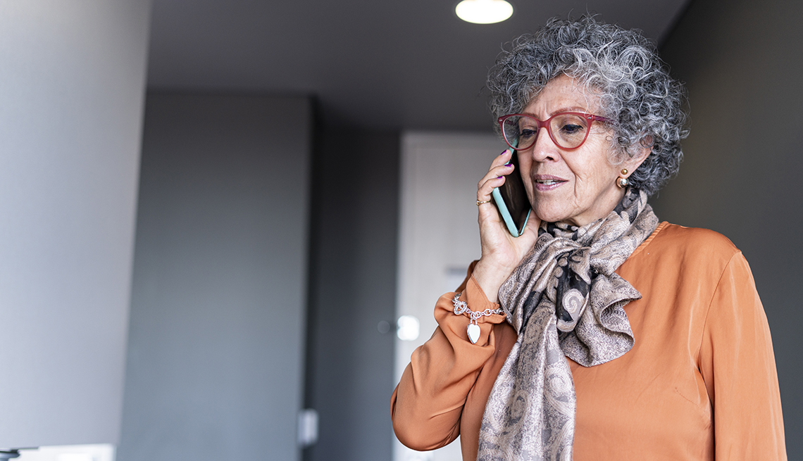 Woman of Latino ethnicity aged between 60-70 years is using the cell phone in times of quarantine by COVID-19