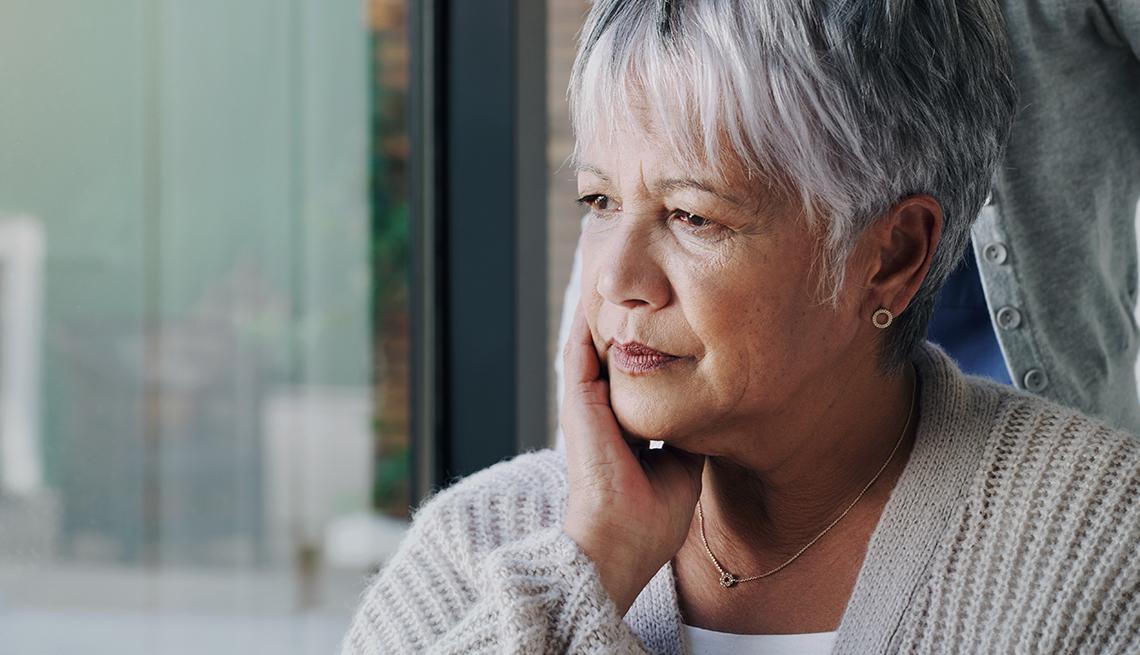 Mujer mira a través de una ventana en una casa de cuidado para personas mayores.