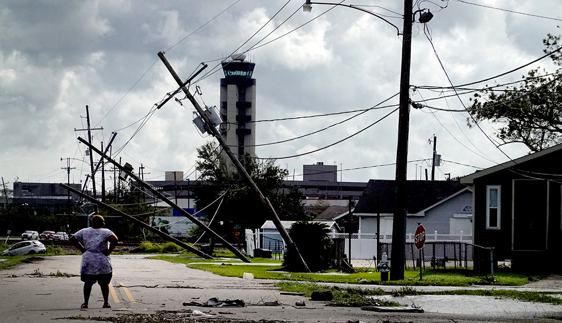 A woman looks over damage to a neighborhood caused by Hurricane Ida on August 30, 2021 in Kenner, Louisiana. Ida