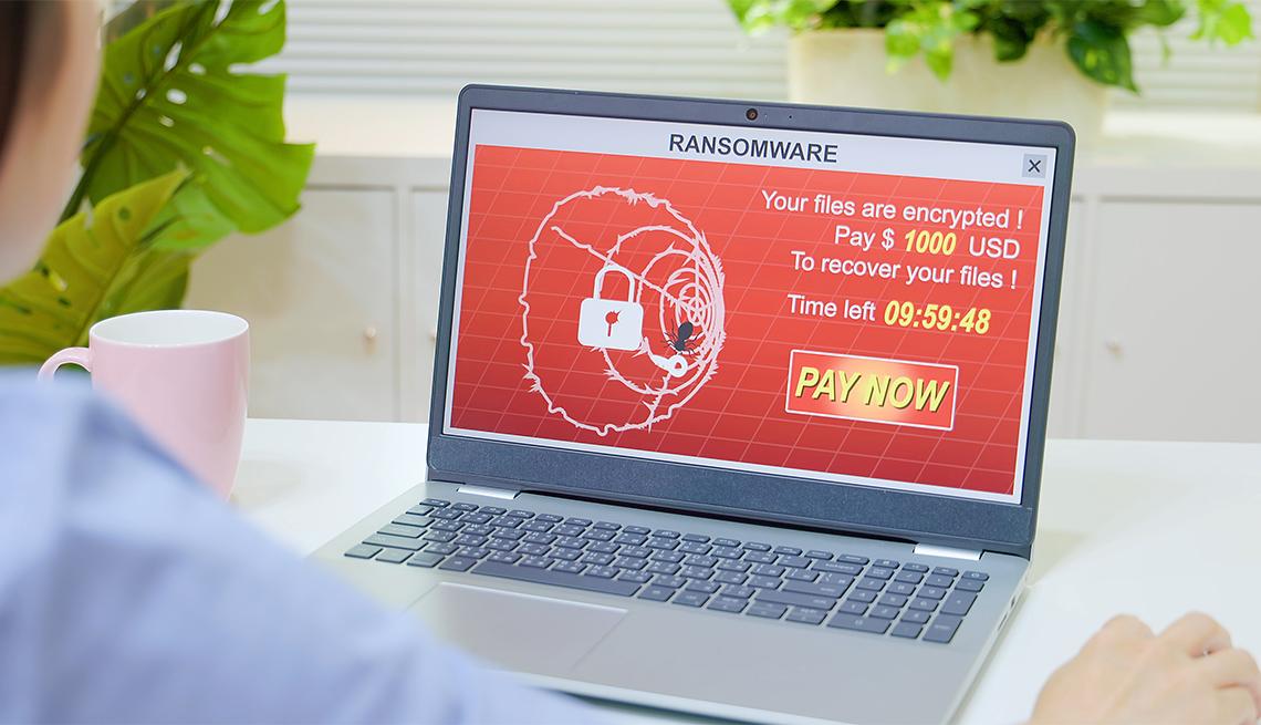 Mujer viendo una imagen que le pide pagar el rescate por el secuestro de su computadora en la pantalla.