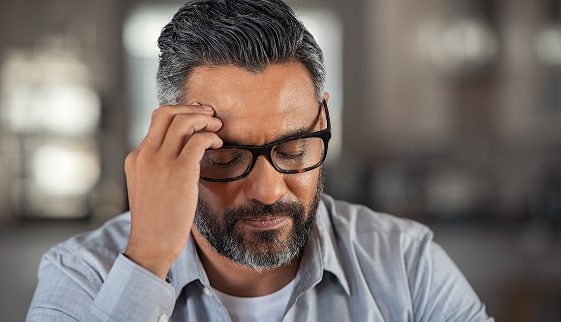Man with hand on head sitting on couch at home. Close up face of stressed indian businessman wearing eyeglasses with eyes closed.