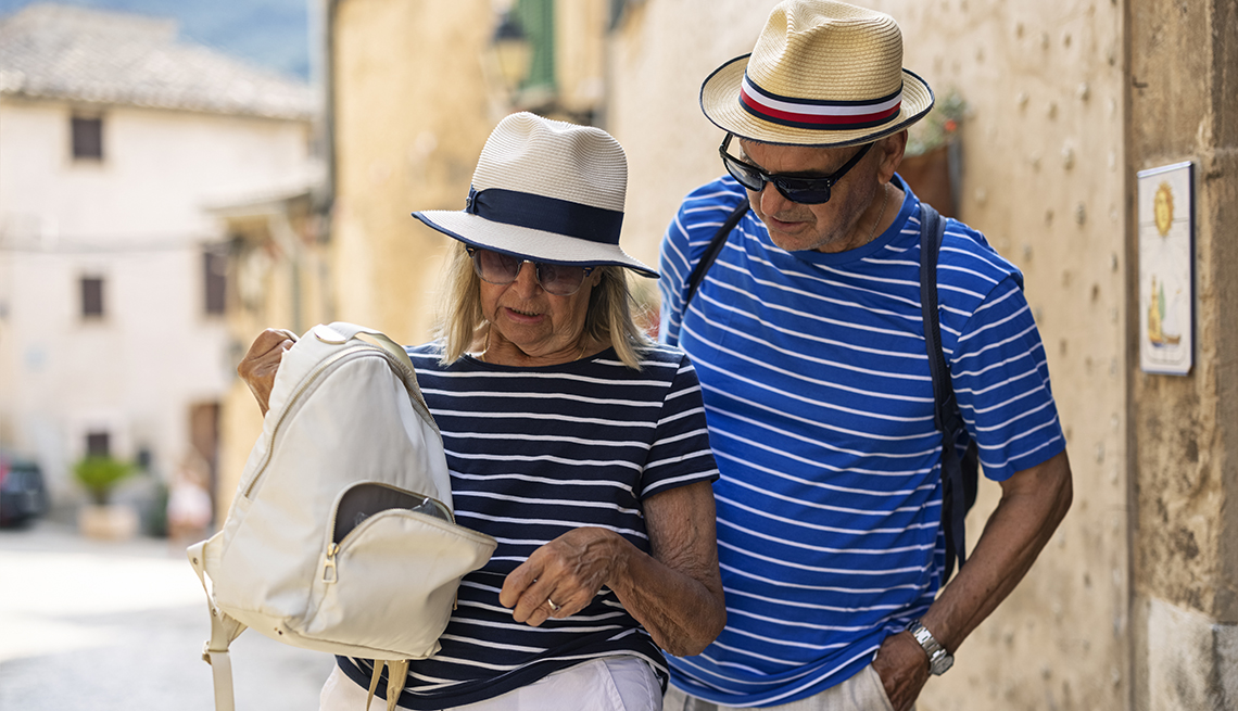 Couple sightseeing a town on summer vacations. The couple is discovering and open backpack and missing wallet.