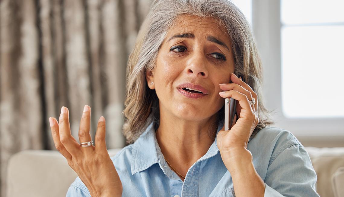 Mujer frustrada al recibir una llamada no deseada en su casa.