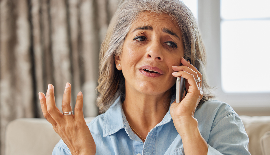Frustrated woman receiving unwanted telephone call at home