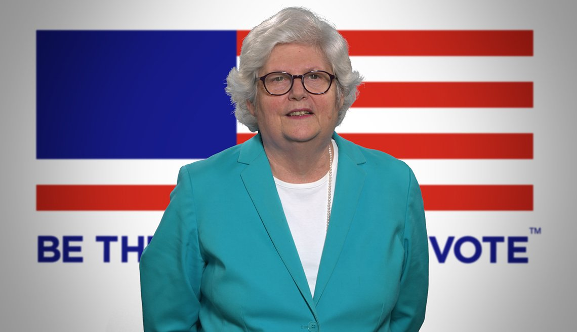 Mature woman standing in front of an image of the flag. Words in the background talk about voting.