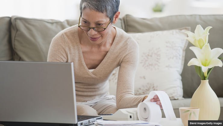 woman paying bills with laptop in living room