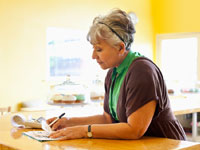A woman pays bills at her kitchen counter