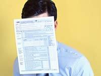 Servicios gratuitos y sitios en línea en español que ayudan a la preparación de impuestos - Hombre se cubre la cara con formulario del IRS.