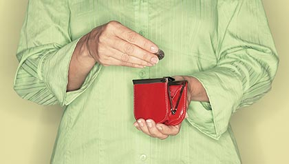 Woman putting a coin into a red purse