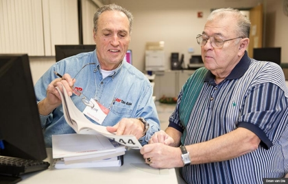 Tax-Aide volunteer Jim Gonzales goes over tax documents with Ray Jimenez