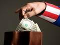 Hombre en traje del tío Sam tomando el dinero de una billetera - Asegúrese de que conoce sus derechos en caso de que el IRS lo contacte acerca de sus impuestos