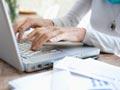 Mujer de edad utilizando un computador portátil mientras la mesa está cubierta de papeles Cómo preparar sus impuestos gratis