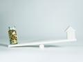 Tarro de monedas y una casa balanceándose - Movimientos de impuestos de fin de año