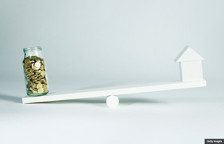 Jar of coins and house balancing. End of year tax moves. (Getty Images)