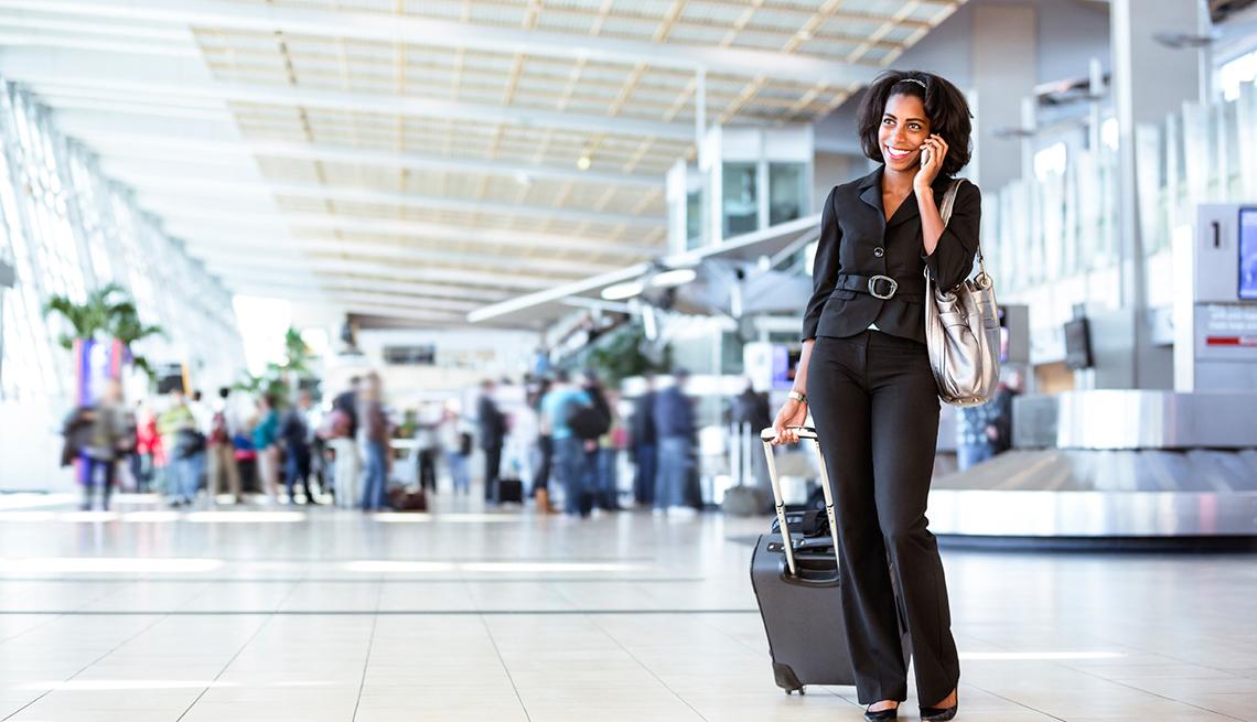 Mujer con una maleta y hablando por teléfono en un aeropuerto.