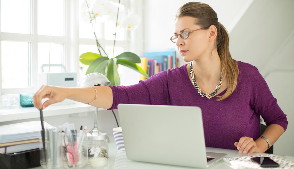 Una mujer frente a una computadora en su oficina en casa.