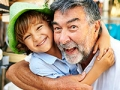 Nieto abrazando a su abuelo - Beneficios del gobierno para abuelos que cuidan nietos.