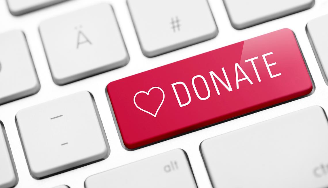Imagen de un teclado con el verbo donar, y si lo haces desde tu plan IRA puedes ahorrar dinero