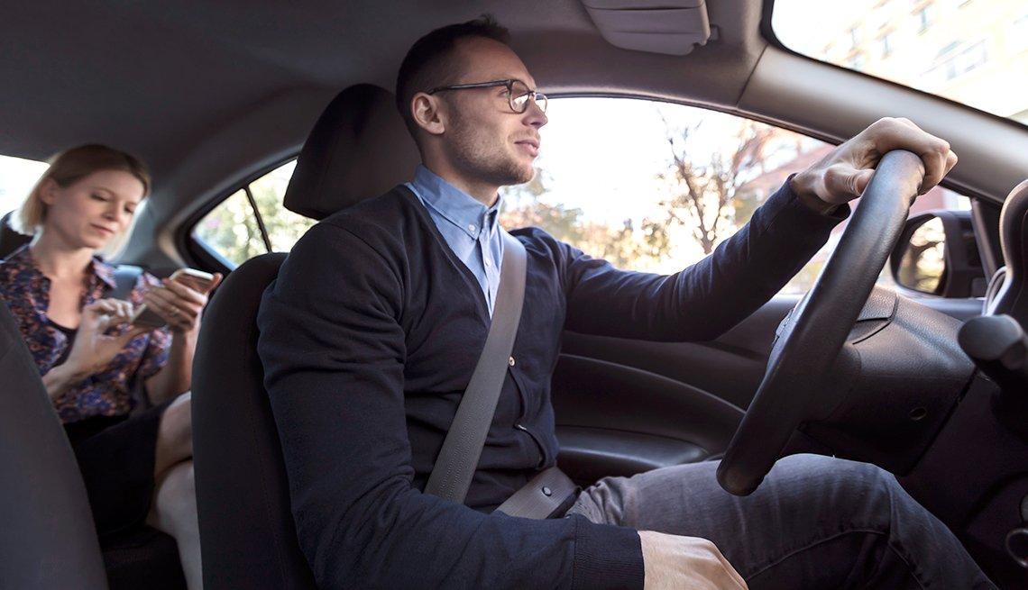 Hombre manejando un carro con una mujer en el asiento trasero.