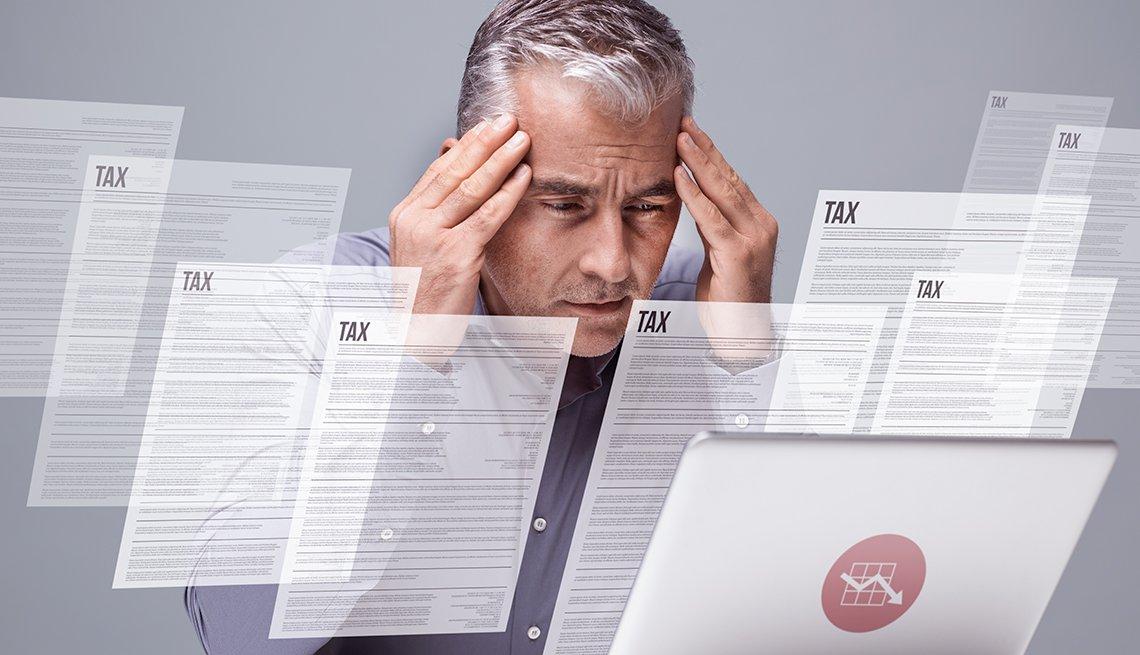 Hombre colocando sus manos a los lados de su frente, viendo una computadora y con papeles flotando