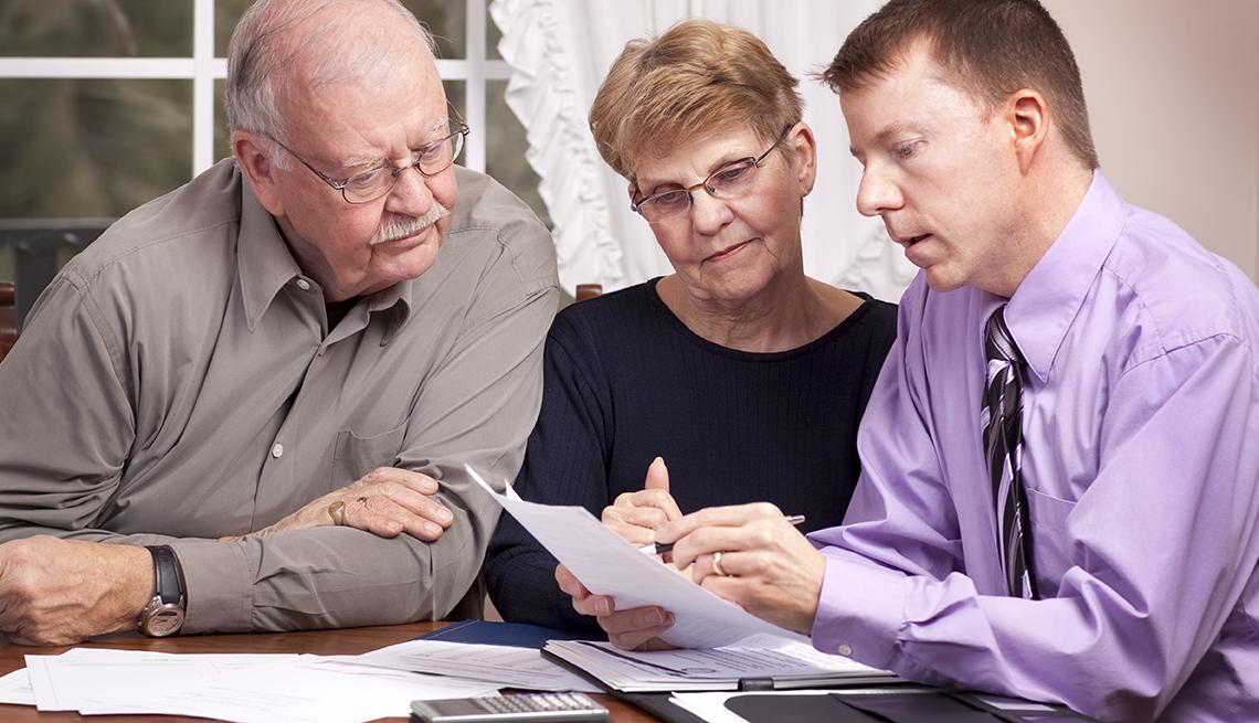 Pareja mayor recibiendo consejos tributarios de un asesor.