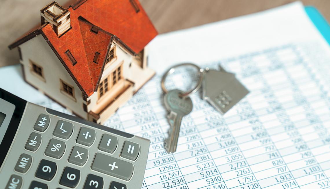 Imagen de una casa pequeña sobre una hoja de cálculo, calculadora y llaves de la casa.