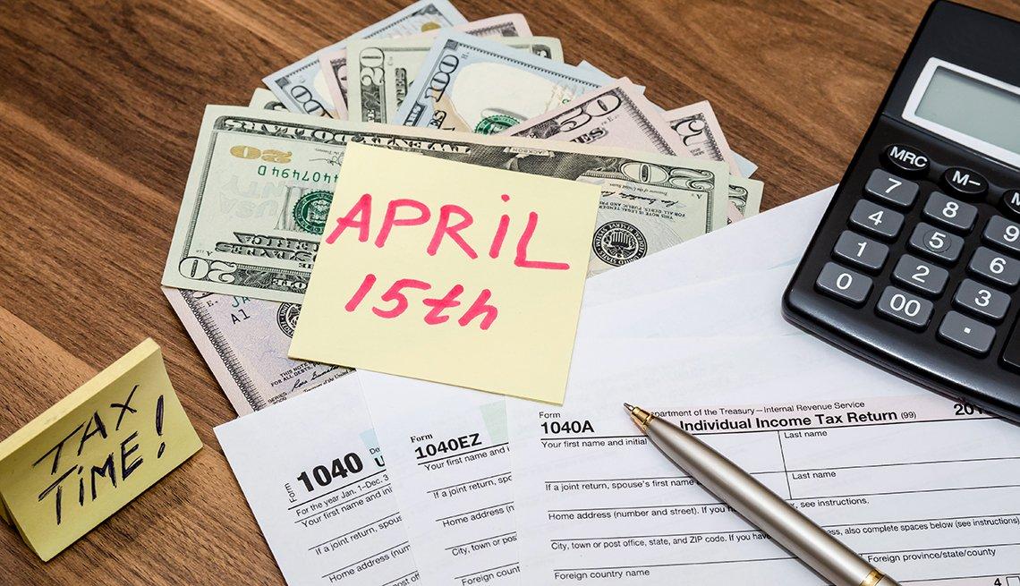 Formulario de impuestos 1040 con una nota adhesiva del 15 de abril