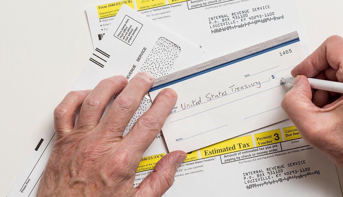 Manos de una persona llenando un cheque de banco.