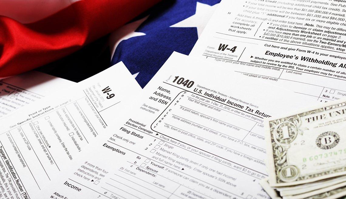 Formularios de impuestos del IRS con unos dólares al lado y la bandera de Estados Unidos