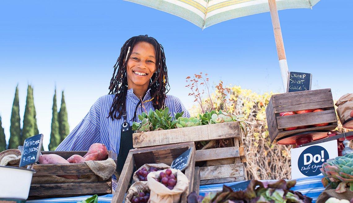 Mujer vendiendo vegetales orgánicos en una feria de mercado.