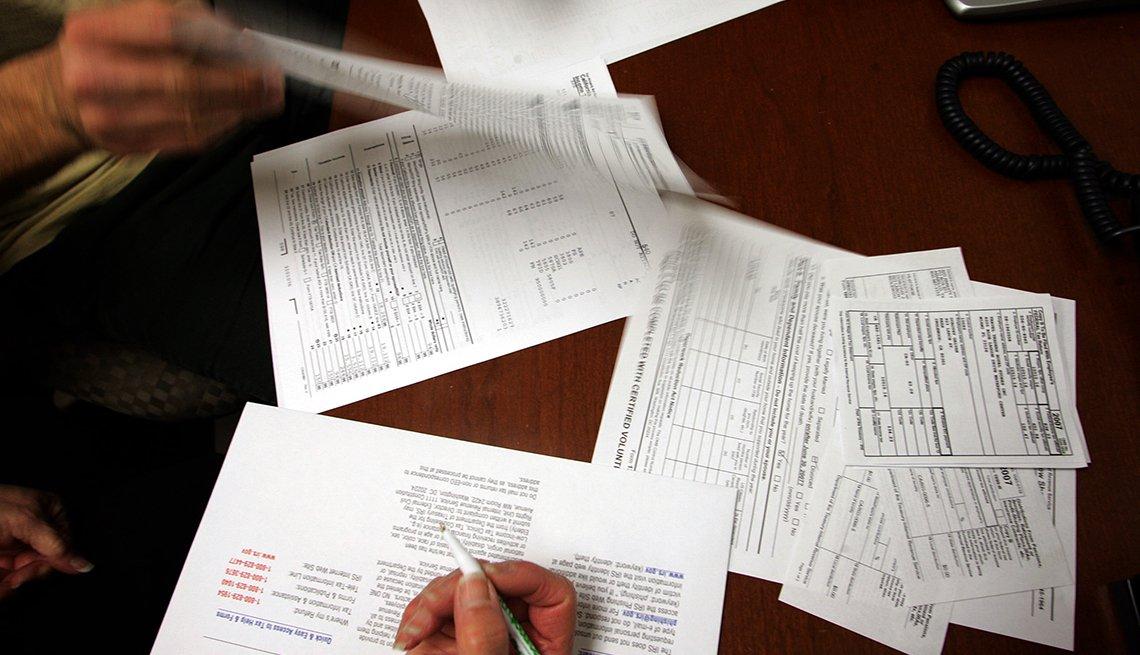 Mesa con formularios de impuestos y las manos de dos personas.