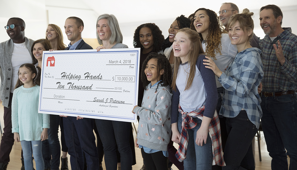 Personas sonriendo y mostrando un cheque gigante de una donación