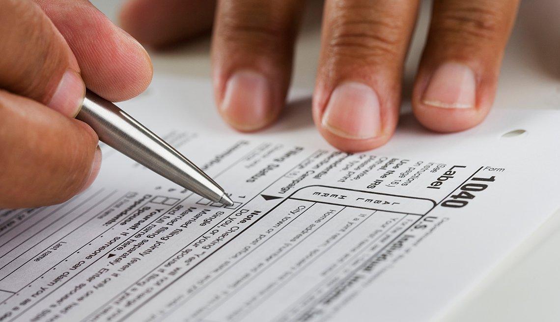 Persona llenando el formulario 1040 del IRS.
