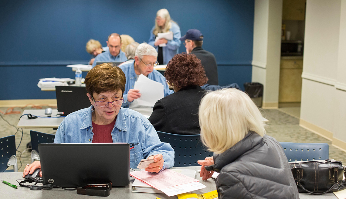 Volunteers from the AARP Foundation sit at computers with clients while preparing income tax returns for low- and moderate-income senior citizens