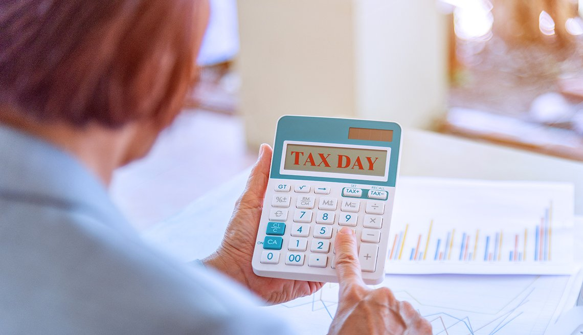 senior working woman holding calculator with tax day words and report data on wood desk