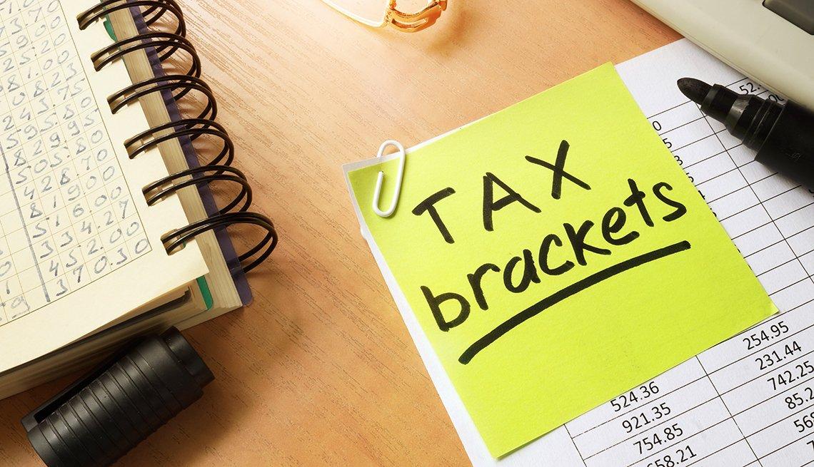 tax brackets post it note on financial spreadsheet
