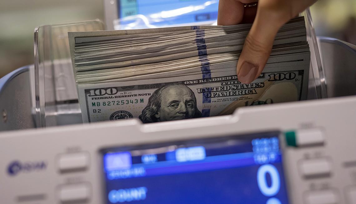 Máquina contando billetes de 100 dólares que son sostenidos por una mano.