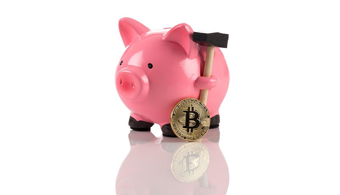 Moneda de bitcóin al lado de una alcancía rosada.