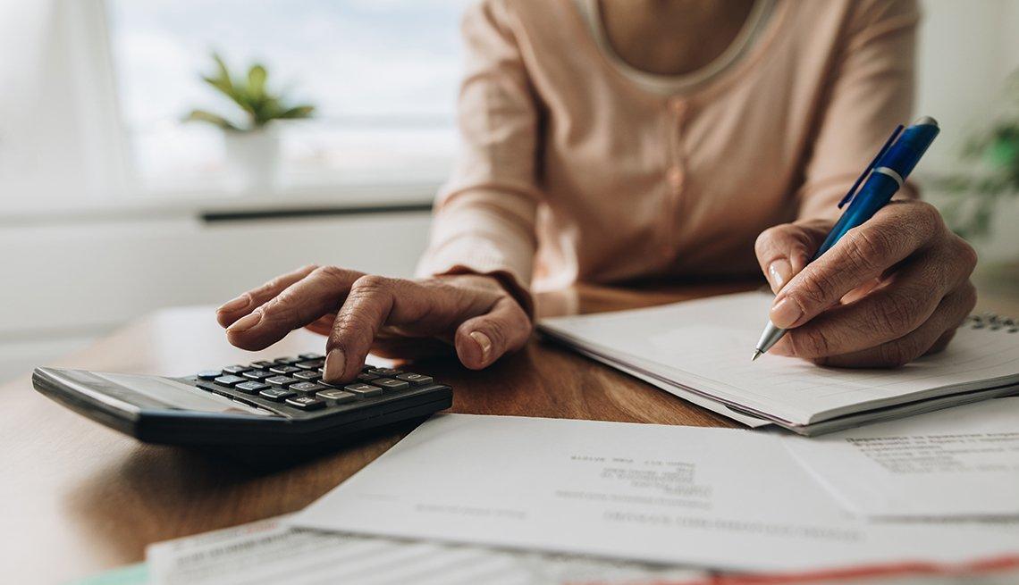 Manos de una mujer haciendo cuentas con una calculadora, papel y lápiz.