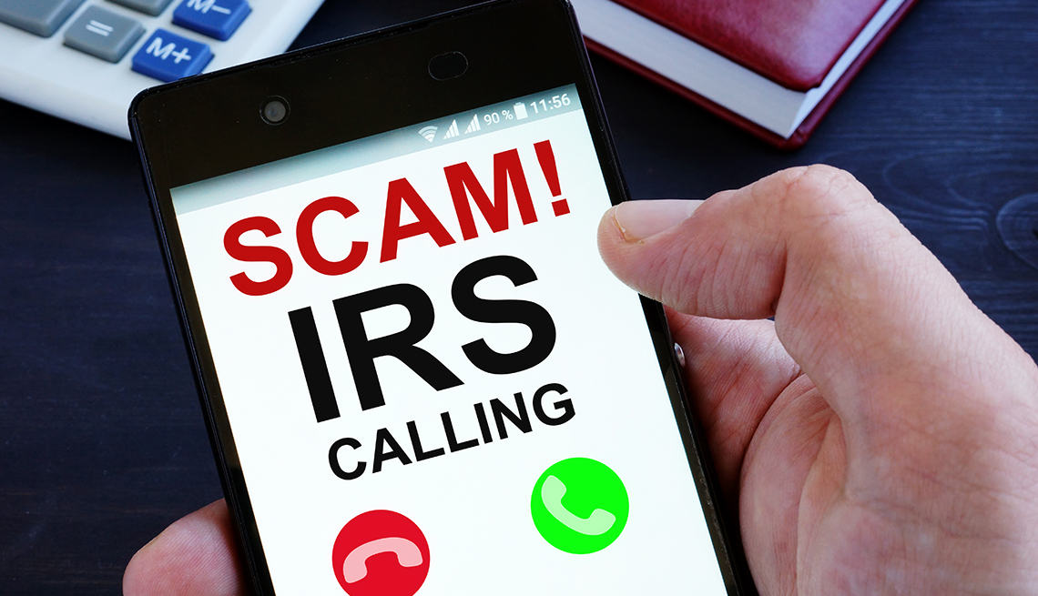 Hand is holding phone with IRS scam calls