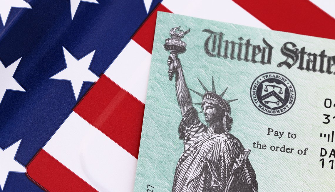 IRS tax refund check on a flag background. Check is showing the Treasury Seal and the Statue of Liberty