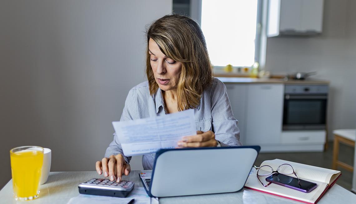 Mujer sentada en una mesa de la cocina haciendo cuentas con calculadora y computadora.