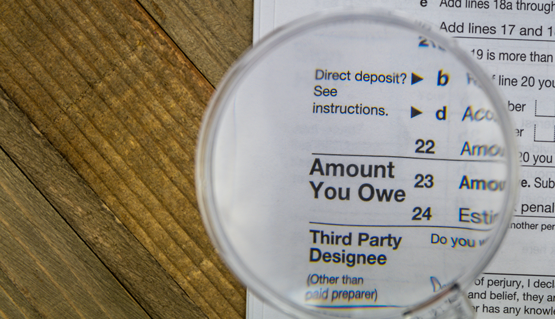 """IRS tax Form on wooden surface with the """"amount you owe"""" section under a magnifying glass"""